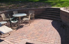 Elegant outdoor living space created using brick patio pavers and landscap block, designed and installed by Exterior Designs of Alexandria