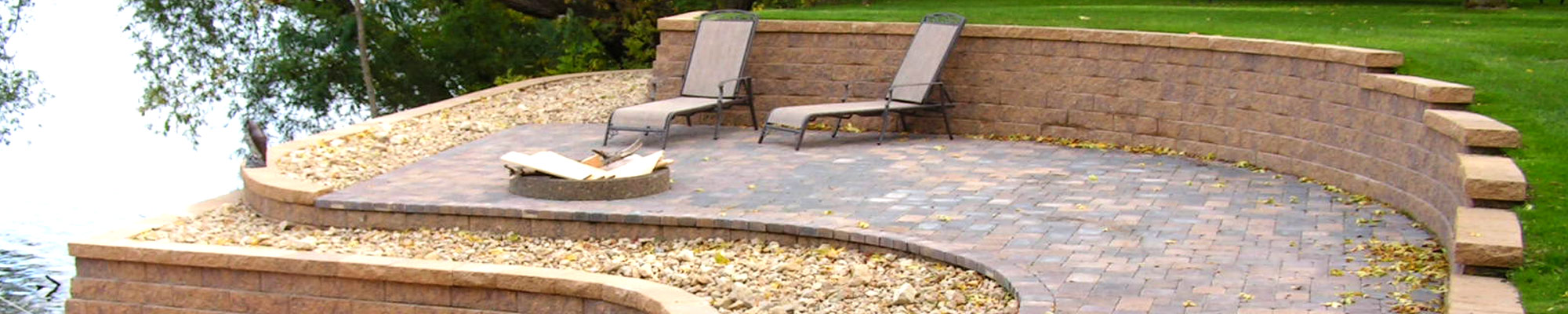 Outdoor living space located along the lakeshore and created using brick patio pavers, multi-tiered retaining walls, and landscape rock